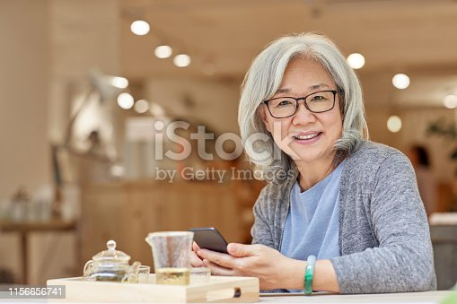 Portrait of smiling senior woman sitting at table. Female is using smart phone in shop. She is casuals.