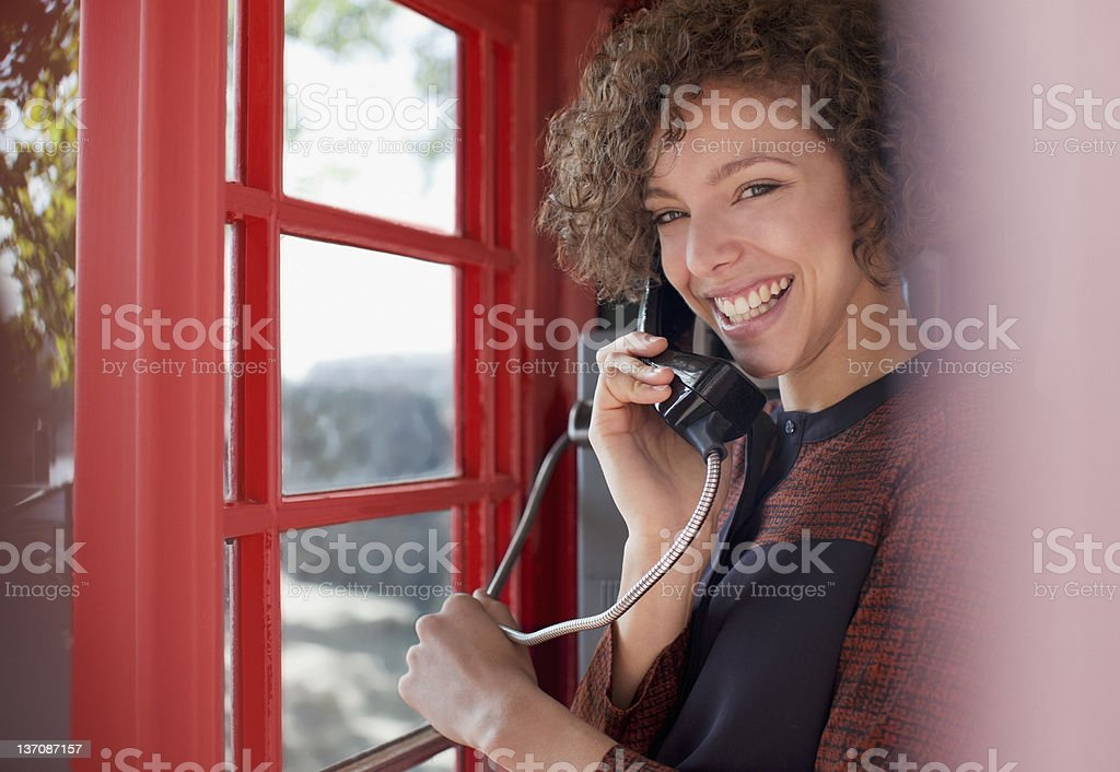 Portrait of smiling woman using telephone booth stock photo