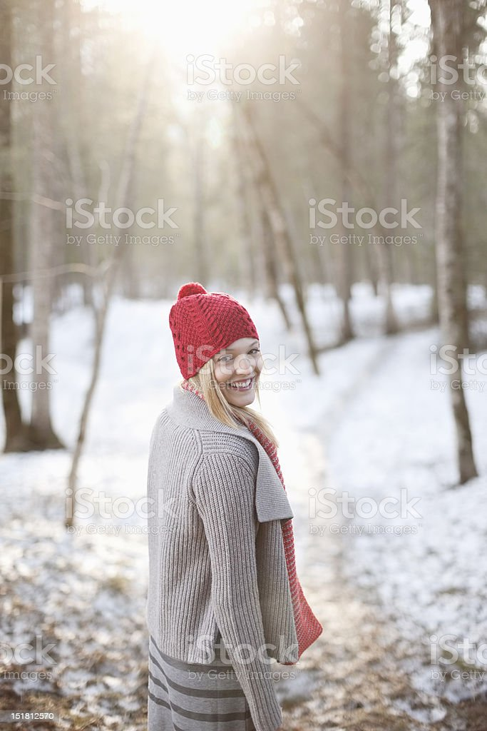 Portrait of smiling woman walking in snowy woods royalty-free stock photo