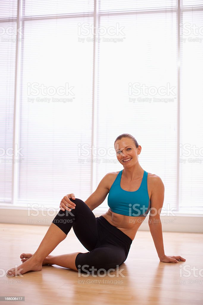 Portrait of smiling woman wearing sports bra in fitness studio royalty-free stock photo