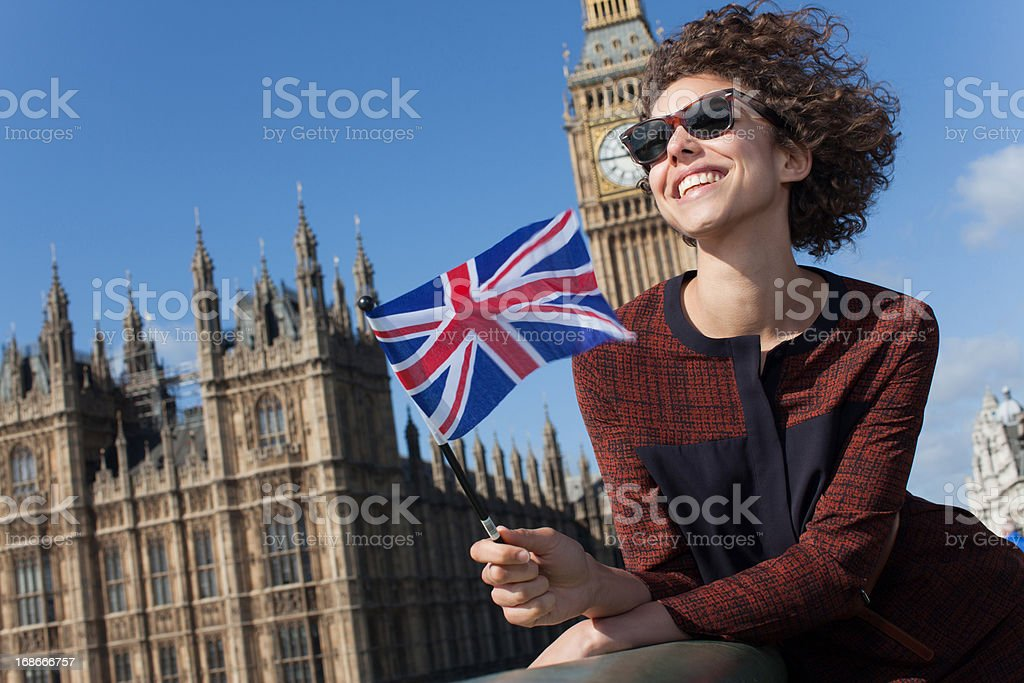 Portrait of smiling woman with British flag in front of Big Ben clocktower royalty-free stock photo