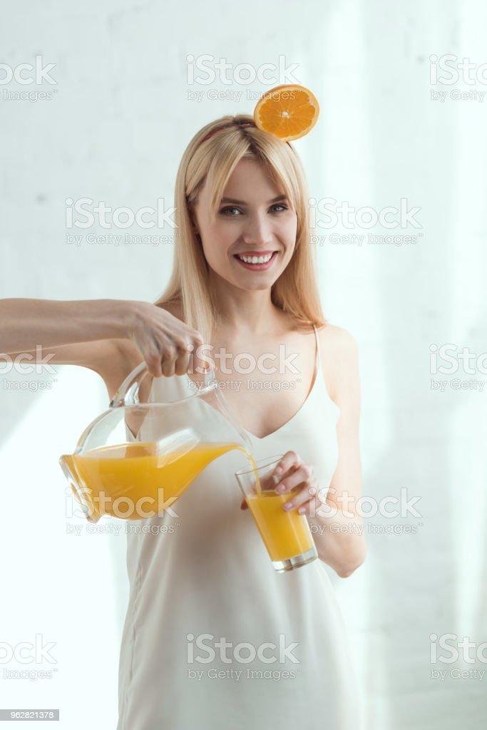 retrato de uma mulher sorridente com pedaço de laranja na cabeça derramando suco em vidro, conceito de estilo de vida vegan - Foto de stock de Adulto royalty-free