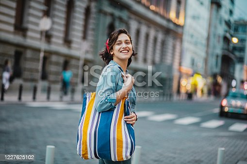 A young modern woman is standing on the street while smiling