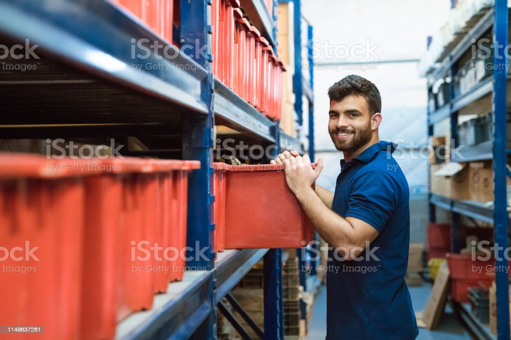 Portrait of smiling worker is working in warehouse Side view portrait of smiling male laborer is working in distribution warehouse. Bearded worker is holding container in factory. He is wearing polo shirt. 20-24 Years Stock Photo