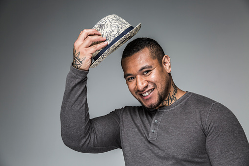 SYD11207: Portrait of smiling young adult pacific islander man with tattoos tipping hat
