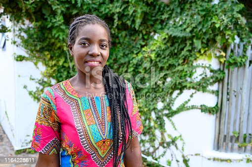 This is a horizontal, color photograph of a beautiful, smiling African woman in her 20s standing outside in South Africa. She is smiling and looking at the camera.