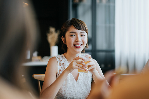 Portrait of smiling young Asian woman having fun and enjoying food and drinks in party with friends