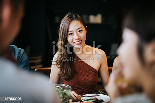 istock Portrait of smiling young Asian woman having fun and enjoying food and drinks in party with friends 1157500206