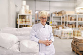 Portrait of smiling young blonde Caucasian blonde woman in sterile uniform and eyeglasses leaning on flour sacks in food factory.