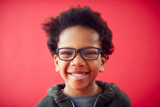 porträtt av leende ung pojke bär glasögon mot röd studio bakgrund - 6 7 år bildbanksfoton och bilder