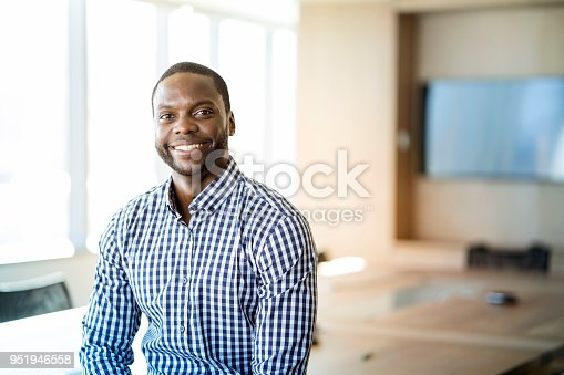 Close-up portrait of smiling businessman. Young male is standing in boardroom. He is wearing blue shirt at office.