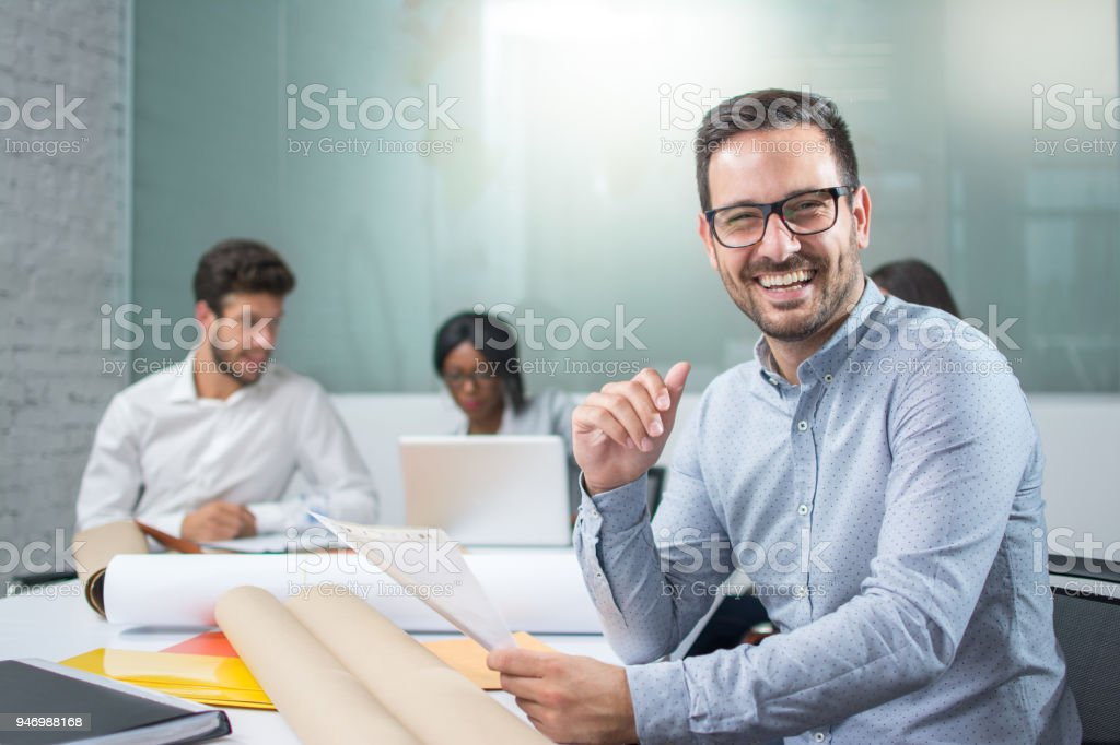 Portrait of smiling young businessman holding paper document and looking at camera in office stock photo