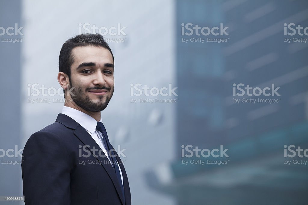 Portrait of smiling young businessman, outdoors, business district stock photo