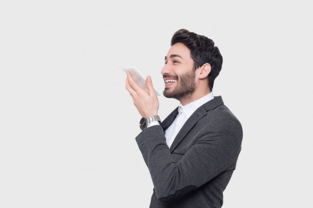 Portrait of smiling young businessman using smart phone's voice recognition against gray background stock photo