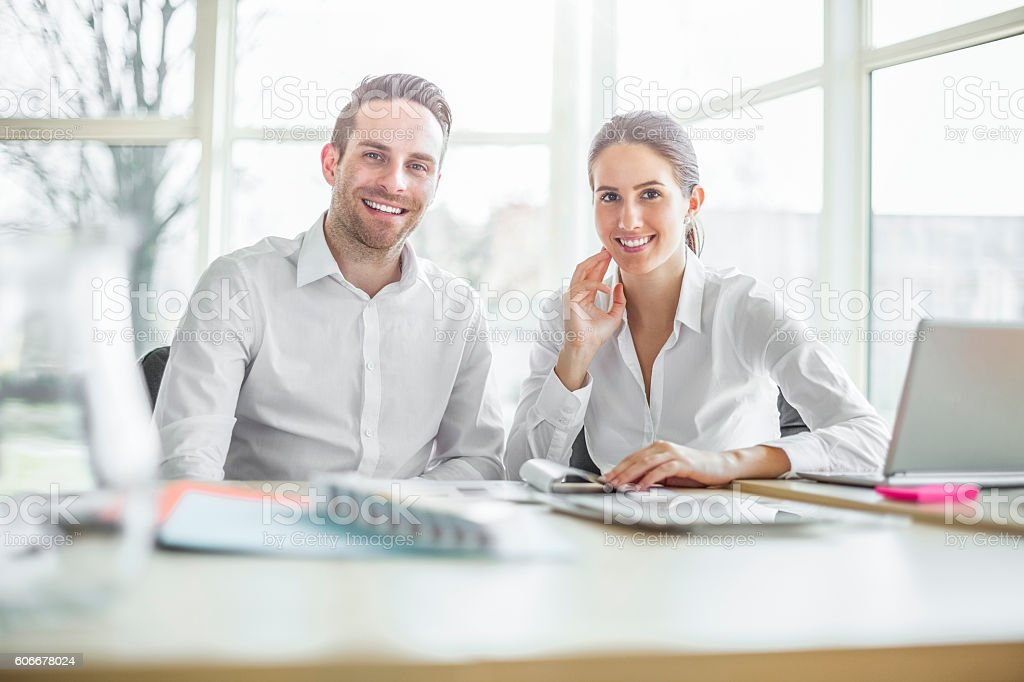Portrait of smiling young businesspeople working at office desk stock photo