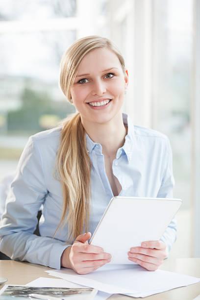 Porträt von lächelnder junger Geschäftsfrau am Schreibtisch – Foto