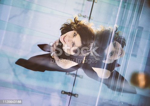 Aerial view of young happiness confident young female owner entrepreneur woman smiling and look at camera posing while sitting floor in a creative luxury office with copy space area. XXXL  Consultant, advisor, small business owner, nutritionist or dietician concepts.