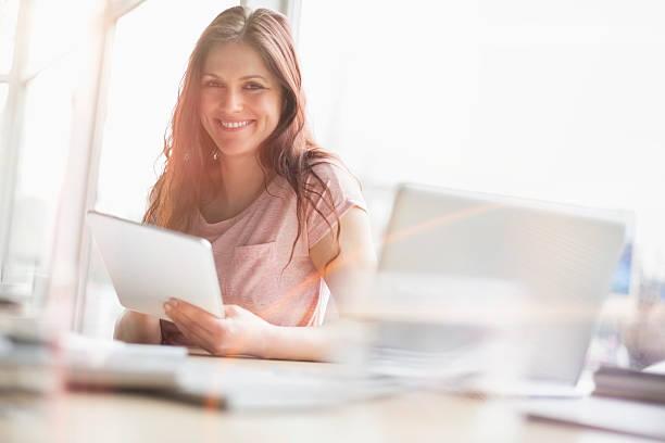 Porträt von lächelnder junger Geschäftsfrau mit Digitaltablett im Büro – Foto