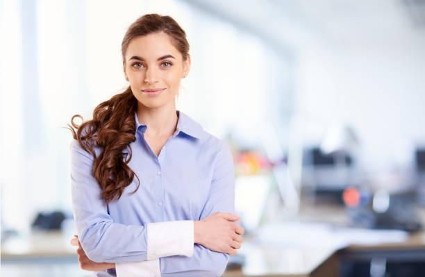 Porträt der lächelnden jungen Geschäftsfrau, während sie im Büro steht – Foto