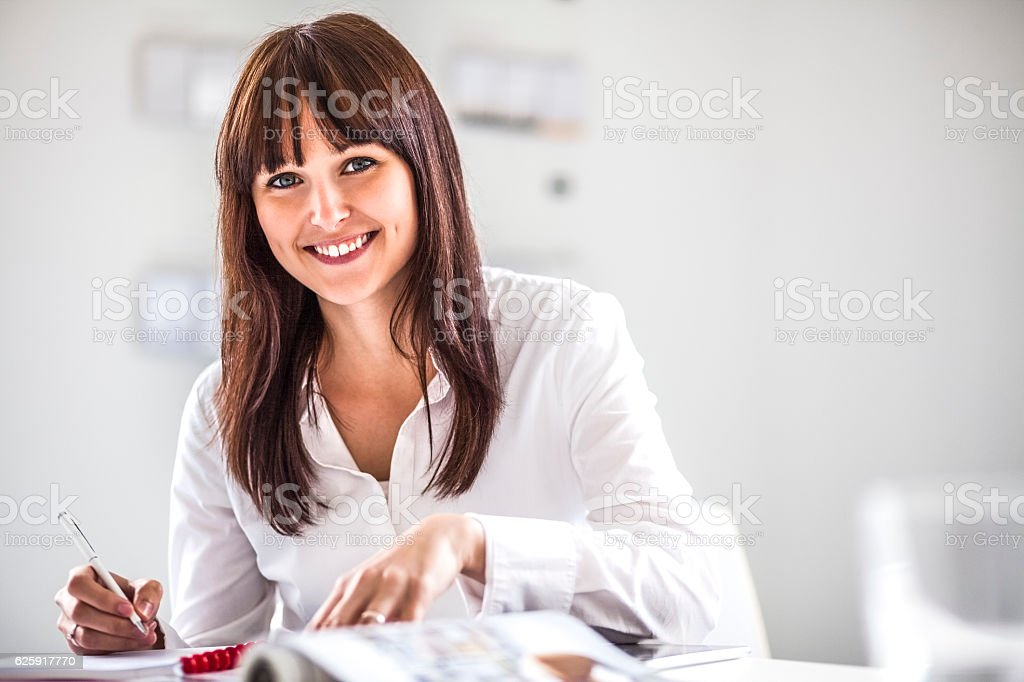 Portrait of smiling young businesswoman working at desk in office – Foto