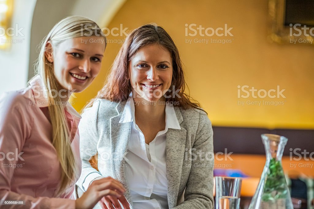 Portrait of smiling young businesswomen in coffee shop stock photo