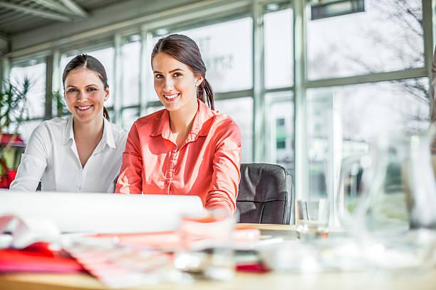 Porträt von lächelnden jungen Geschäftsfrauen Arbeiten am Schreibtisch im Büro – Foto