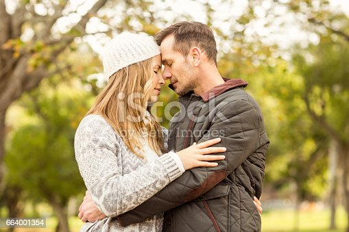 istock Portrait of smiling young couple embracing 664001354