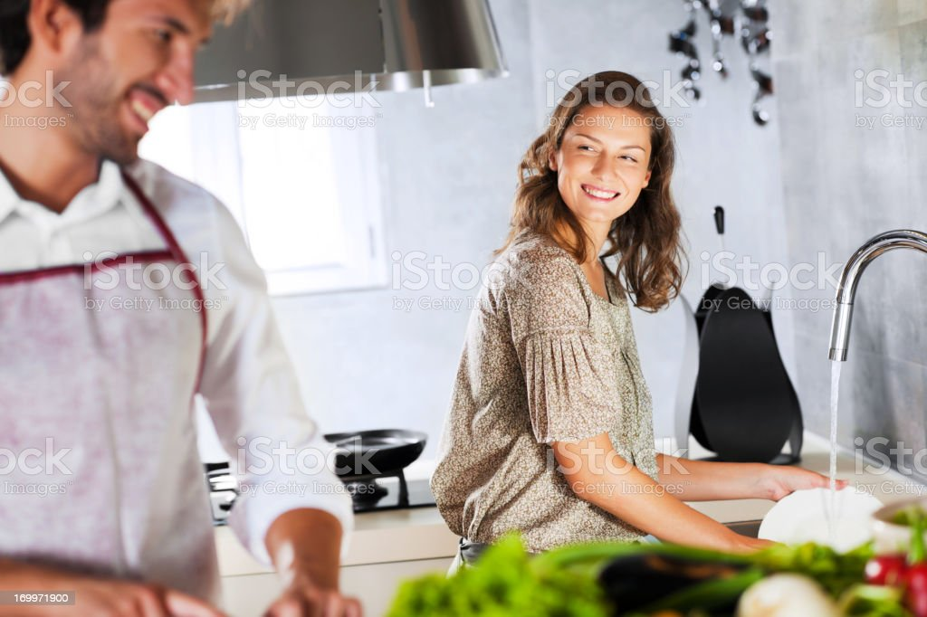 Portrait of smiling young couple preparing lunch together stock photo