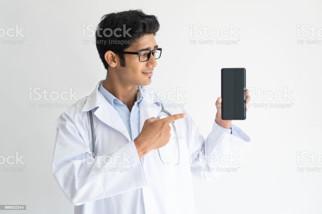 Portrait of smiling young doctor in glasses showing mobile phone stock photo