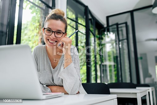 Portrait of smiling young female student in eyeglasses sitting in modern library.
