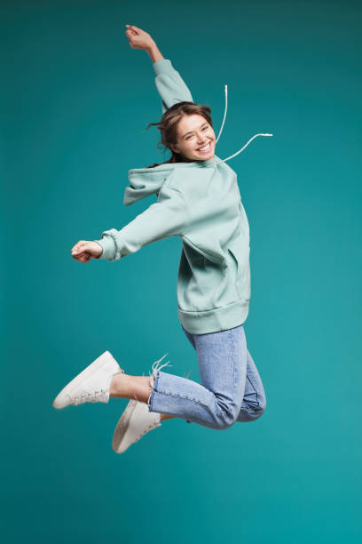 Portrait of smiling young female student in tender blue hoodie jumping up with raised arms stock photo
