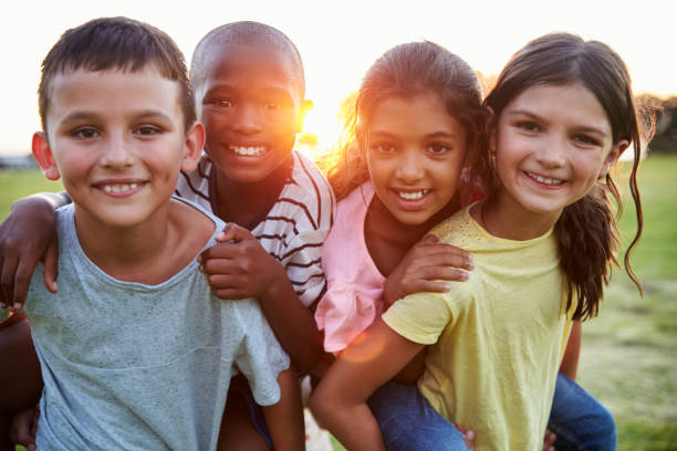 Portrait of smiling young friends piggybacking outdoors Portrait of smiling young friends piggybacking outdoors children only stock pictures, royalty-free photos & images