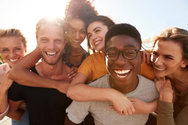 Retrato de jóvenes amigos sonriendo caminando al aire libre juntos - foto de stock