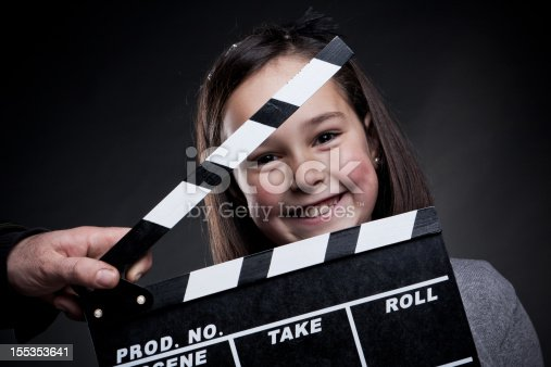 istock Portrait of smiling young girl behind a movie clapper board 155353641
