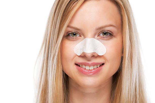 portrait of smiling young girl with clear-up strips on nose stock photo