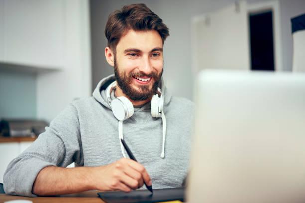 Porträt eines lächelnden jungen Grafikdesigners, der von zu Hause aus arbeitet – Foto