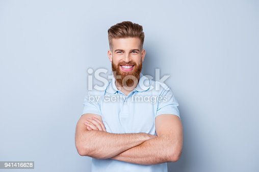 istock Portrait of smiling young happy bearded man in polo isolated on gray backdrop 941416628
