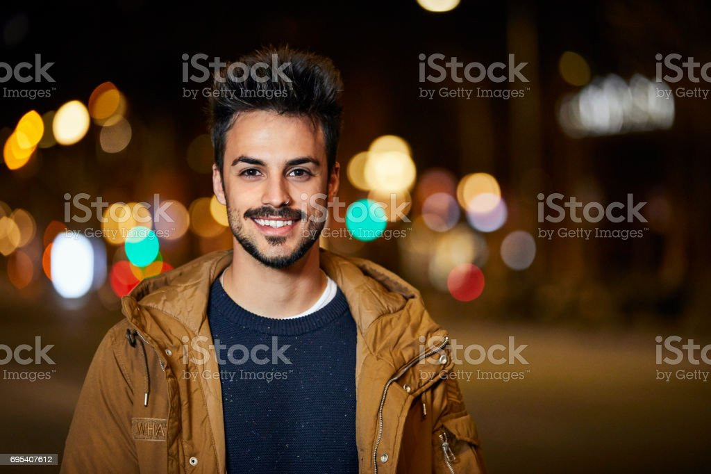 Portrait of smiling young man in city at night stock photo