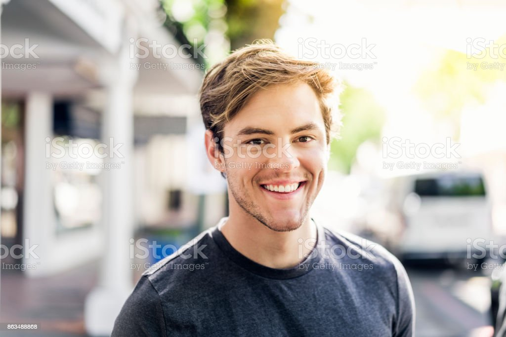 Portrait of smiling young man in city on sunny day stock photo