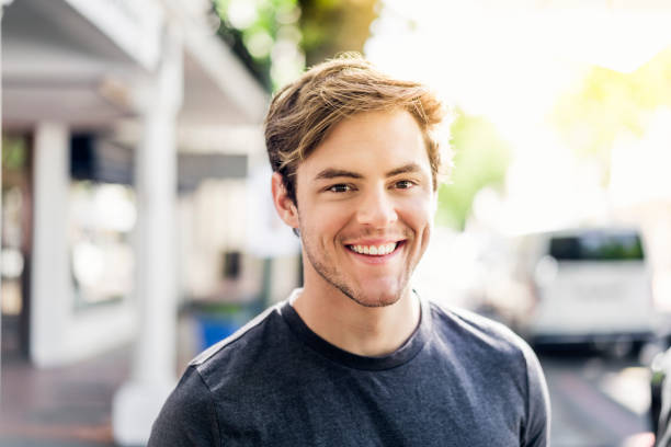 Portrait of smiling young man in city on sunny day - foto stock