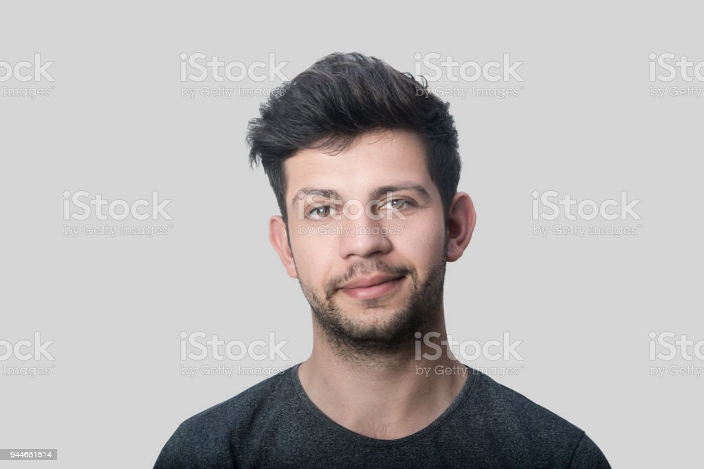 Portrait of smiling young man looking at camera over gray background stock photo