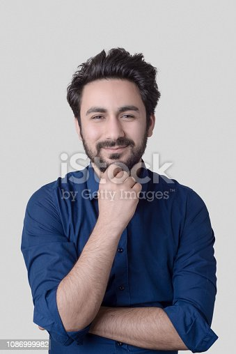 istock Portrait of smiling young man over gray background 1086999982