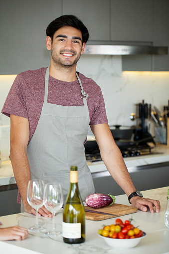 Portrait of smiling young man standing in kitchen