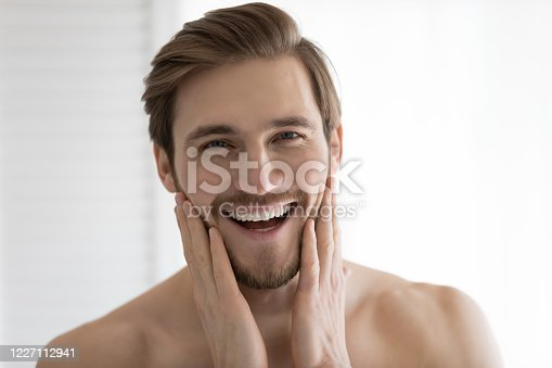 Close up headshot portrait of overjoyed young caucasian man touch healthy clean face after shaving, smiling millennial male satisfied with facial treatment, apply cream or balm, skincare concept
