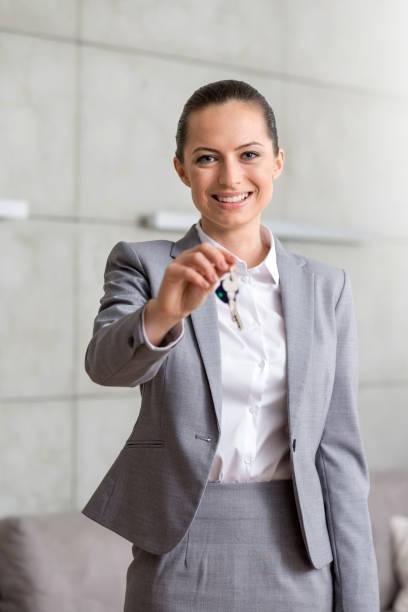 Porträt der lächelnden jungen Verkäuferin, die Hausschlüssel gibt, während sie in der Wohnung gegen die Wand steht – Foto
