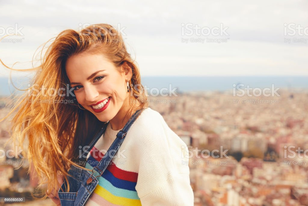 Portrait of smiling young woman against cityscape stock photo