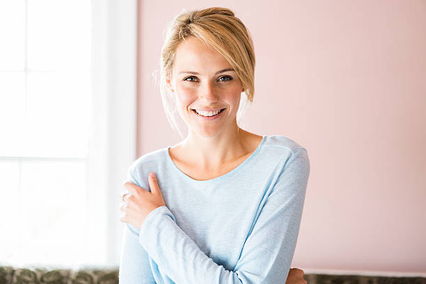 Portrait of smiling young woman at home stock photo