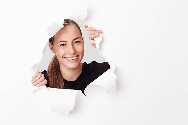 Portrait of smiling young woman emerging from paper stock photo