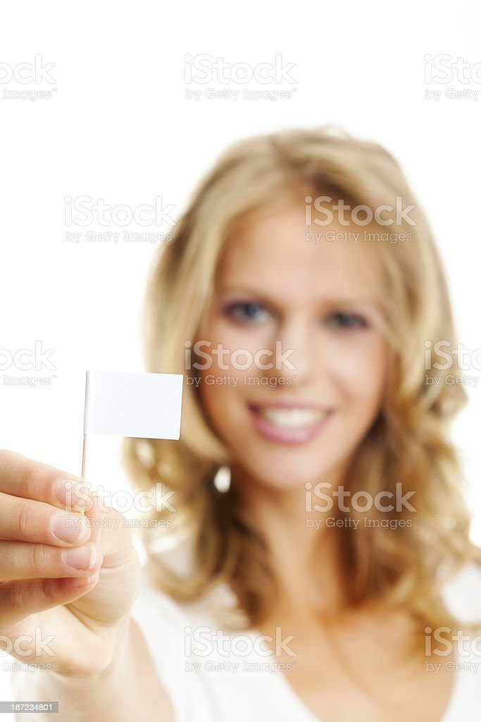 Portrait of smiling young woman holding a small Whilte flag. royalty-free stock photo