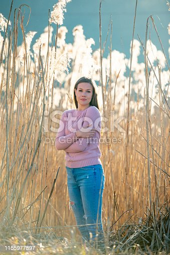 Portrait of Smiling Young Woman in Casual Clothing in Rural Scene.